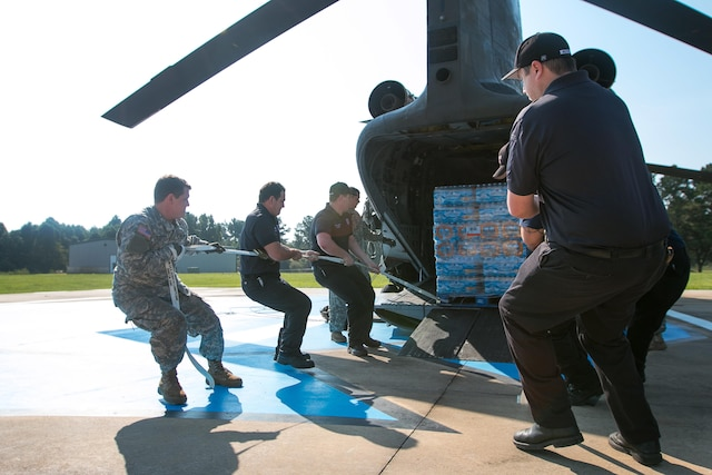 Soldiers work alongside the Liberty Fire Department to unload pallets of water from a CH-47 Chinook helicopter