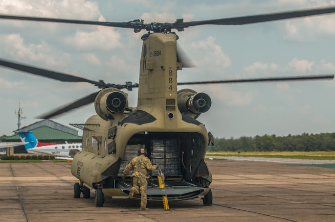 A soldier packs bottled water into the back of a helicopter.