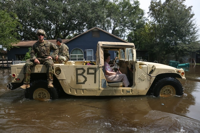 A military vehicle carries a rescued woman and soldiers through flooded streets.