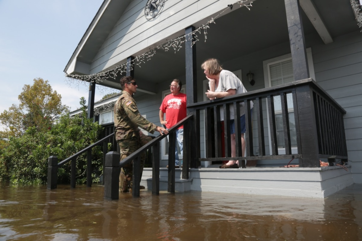 A soldier stands on the steps of a flooded house talking to two residents on the porch.