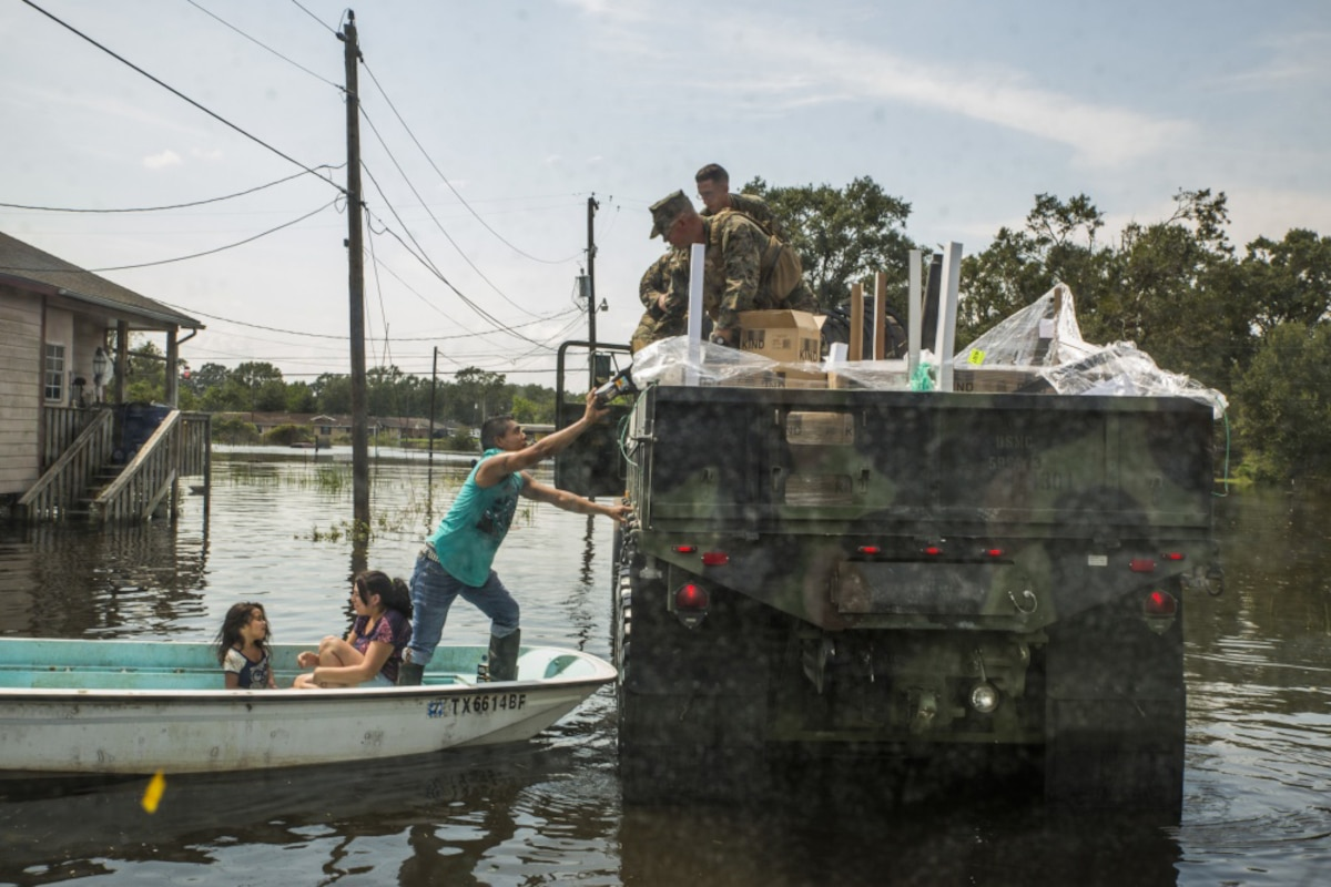 Marines on a military vehicle hand supplies to a man standing on a boat that is also carrying two young girls.