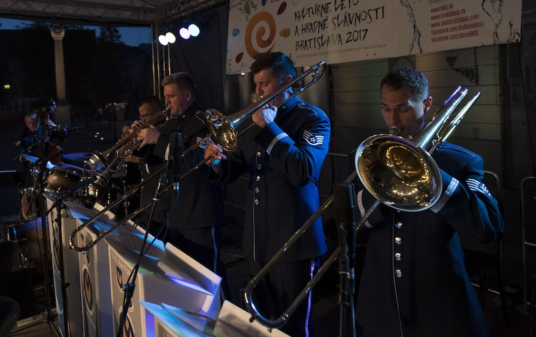 Trombone and trumpet players in the U.S. Air Forces in Europe jazz band play their instruments during a concert for the 73rd anniversary of the Slovak National Uprising in Bratislava, Slovakia, Aug. 30, 2017. U.S. bands are invited each year to perform for the celebration. Participating in events with NATO allies improves interoperability and strengthens long standing relationships. (U.S. Air Force photo by Senior Airman Tryphena Mayhugh)
