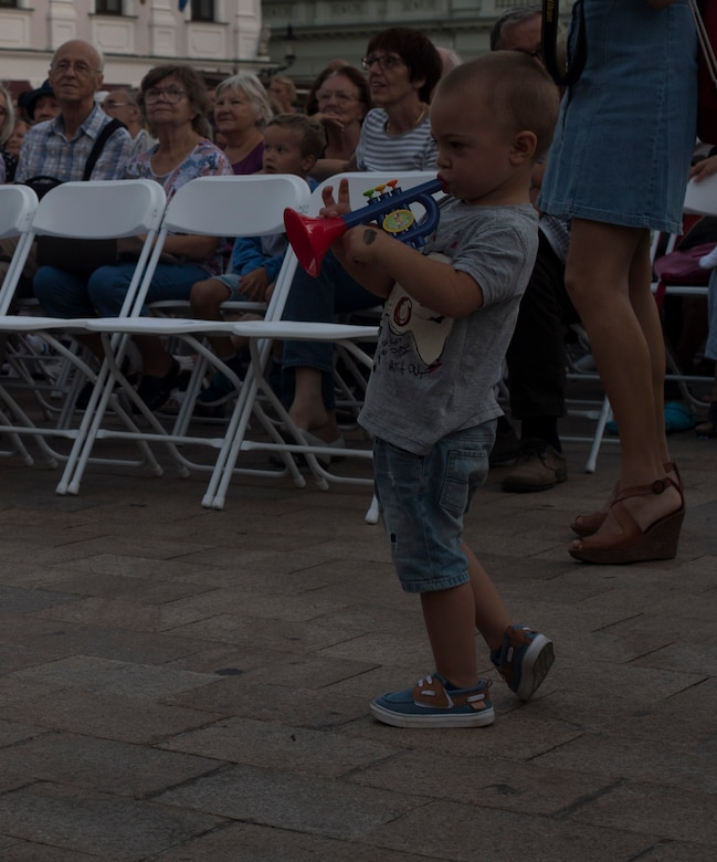 A child plays a toy trumpet along with the U.S. Air Forces in Europe jazz band as they perform a concert for the 73rd anniversary of the Slovak National Uprising in Bratislava, Slovakia, Aug. 30, 2017. The USAFE band represents unique international musical heritage, building and preserving partnerships through official multi-national military and international community outreach events. (U.S. Air Force photo by Senior Airman Tryphena Mayhugh)