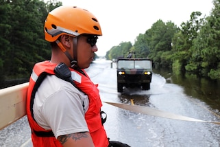A guardsman looks at a flooded street with a military vehicle in the background.
