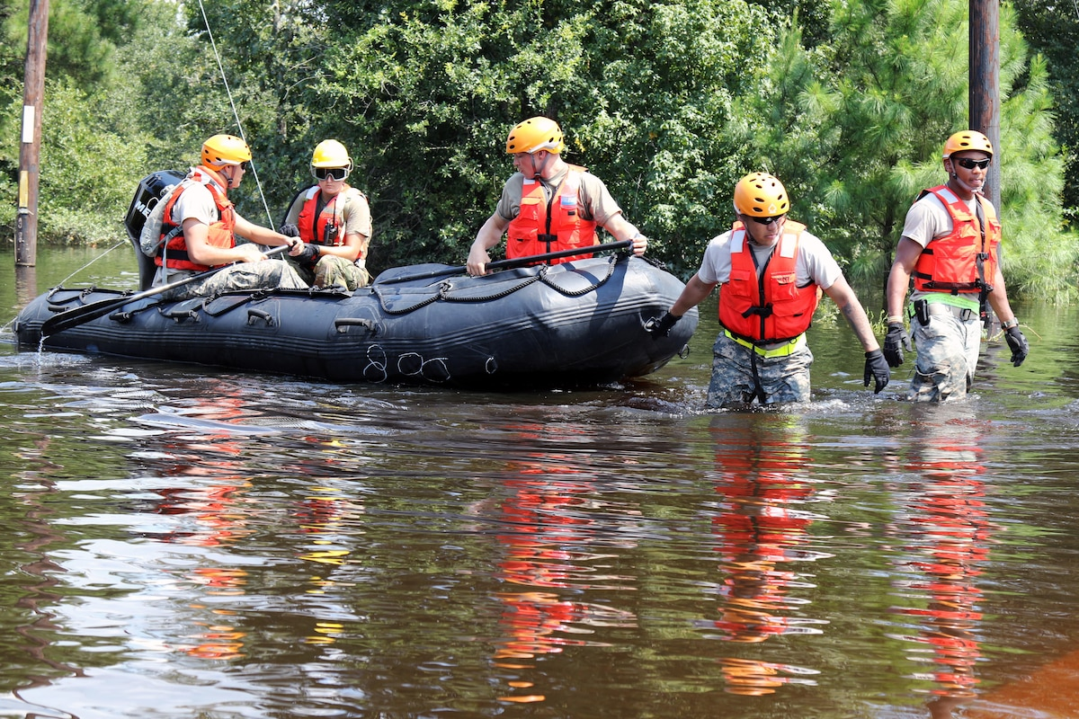 A group of guardsmen wade through floodwaters pulling a boat with three other guardsmen.