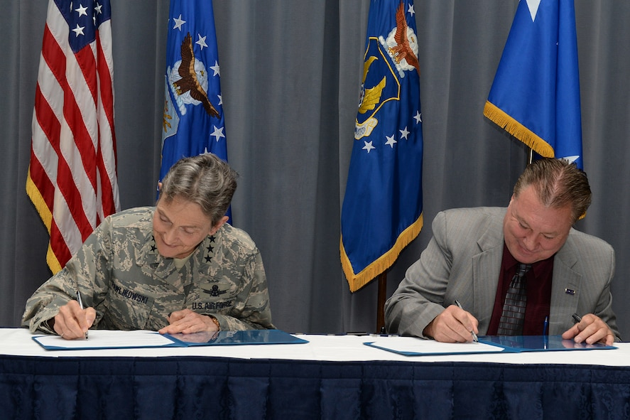Gen. Ellen M. Pawlikowski, Air Force Materiel Command commander, and Troy Tingey, American Federation of Government Employees Council 214 president, add their signatures to the Master Labor Agreement during a signing ceremony at Headquarters Air Force Materiel Command Aug. 23, 2017. (U.S. Air Force photo/Michelle Gigante)