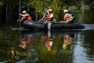 Four soldiers paddle a boat in floodwaters.