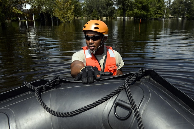 A soldier stands in floodwaters with his hand on a boat.