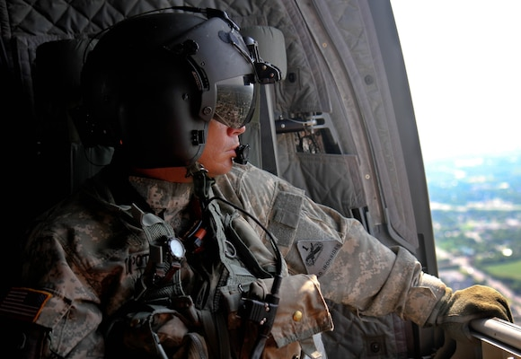 Sgt. 1st Class Aaron Potter, a CH-47 helicopter repairer with 2nd Battalion, 501st Aviation Regiment from Fort Bliss, Texas, overlooks the devastation from a CH-47 Chinook in Houston caused by Hurricane Harvey Sept. 3. Potter was a part of a supply mission under the newly-stood up Task Force Aviation to unload 24,192 bottles of water in support of the people affected in Beaumont, Texas.