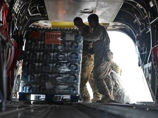 Sgt. 1st Class Aaron Potter, a CH-47 helicopter repairer with 2nd Battalion, 501st Aviation Regiment from Fort Bliss, Texas, pushes a pallet of water on a CH-47 Chinook Sept. 3 at Joint Base San Antonio-Auxiliary Airfield in Seguin, Texas, for a supply deliver to citizens affected by Hurricane Harvey.