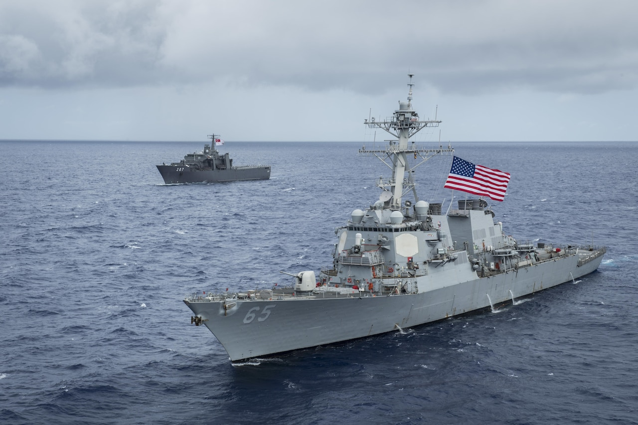 Two military ships take part in an exercise off the coast of Guam.