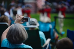 """An attendee records the U.S. Army Old Guard Fife and Drum Corps performance at the season finale of the """"Music Under the Stars"""" concert series at Joint Base Langley-Eustis, Va., Aug. 31, 2017."""