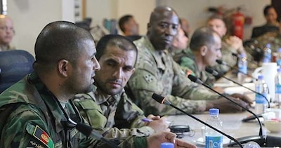 Afghan Air Force Academy Command Sgt. Maj. Bakhshi Amo and Afghan Ministry of Interior Command Sgt. Maj. Sayd Hasibullah speak at the Warfighter Forum, a quarterly gathering of senior enlisted leaders, to share their experiences and continue improving the Afghan national defense and security forces. Navy photo by Lt. j.g. Egdanis Torres Sierra