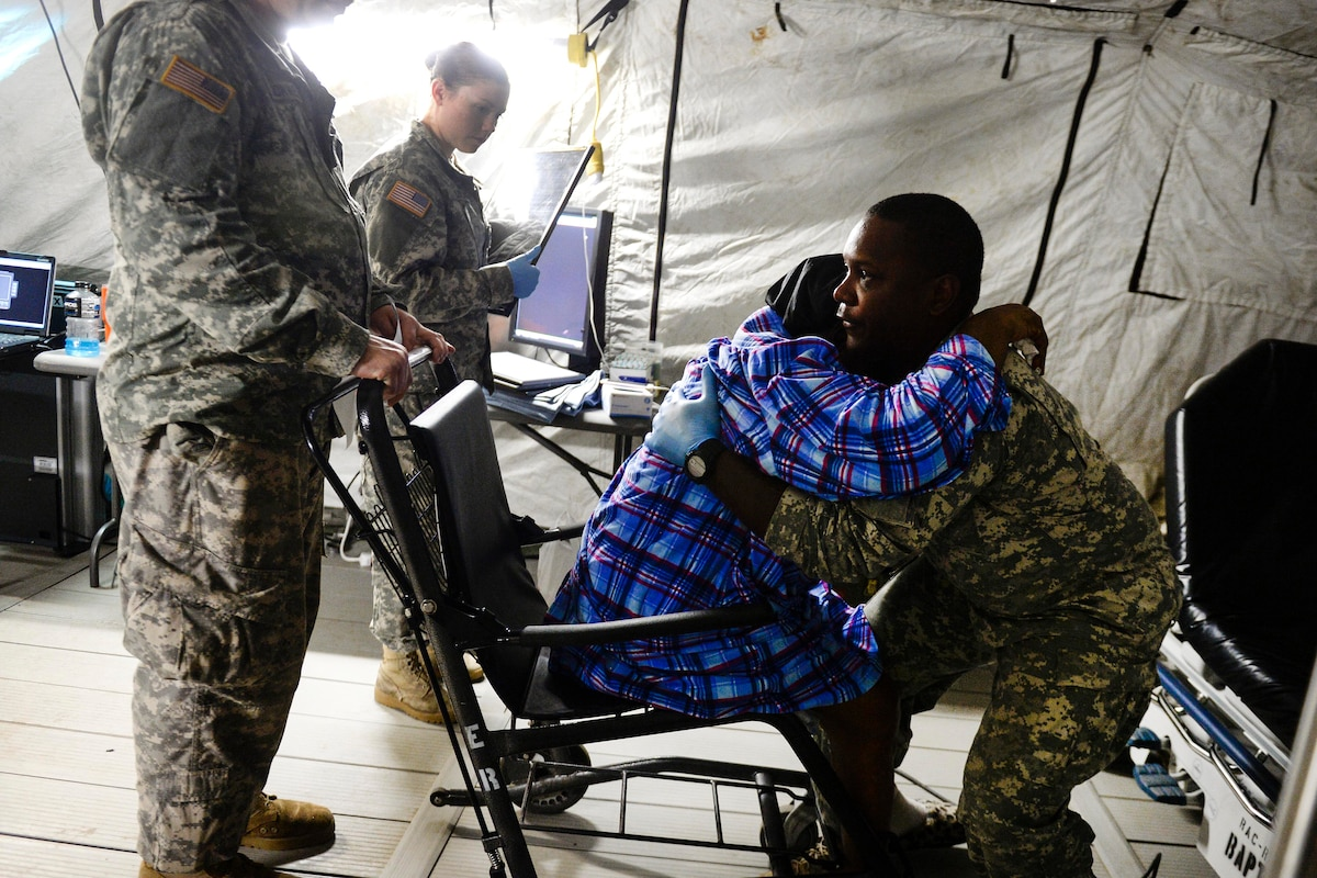 Three soldiers help a woman out of a wheel chair.