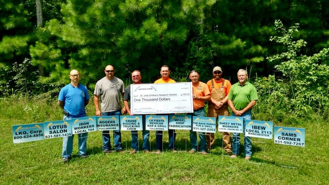 AEDC team members display the $1,000 check representing funds raised for the St. Jude Children's Research Hospital through the Lightning Classic Golf Tournament Aug. 4 at the Willowbrook Golf Club. AEDC team members pictured, with sponsor signs, are Bruce Prater, Shannon Tate, Stacy Parker, Roy Mullins, Steven Meeks, Colby Cox and Barry McWhorter. (Courtesy photo)