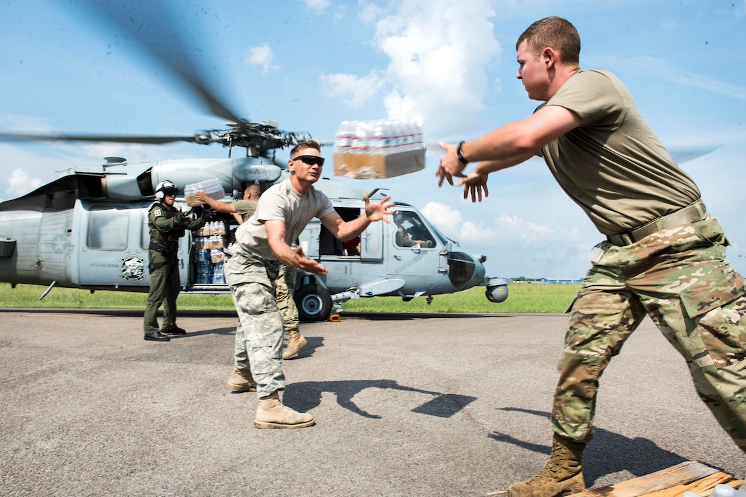 Soldiers and sailors load water onto a helicopter.