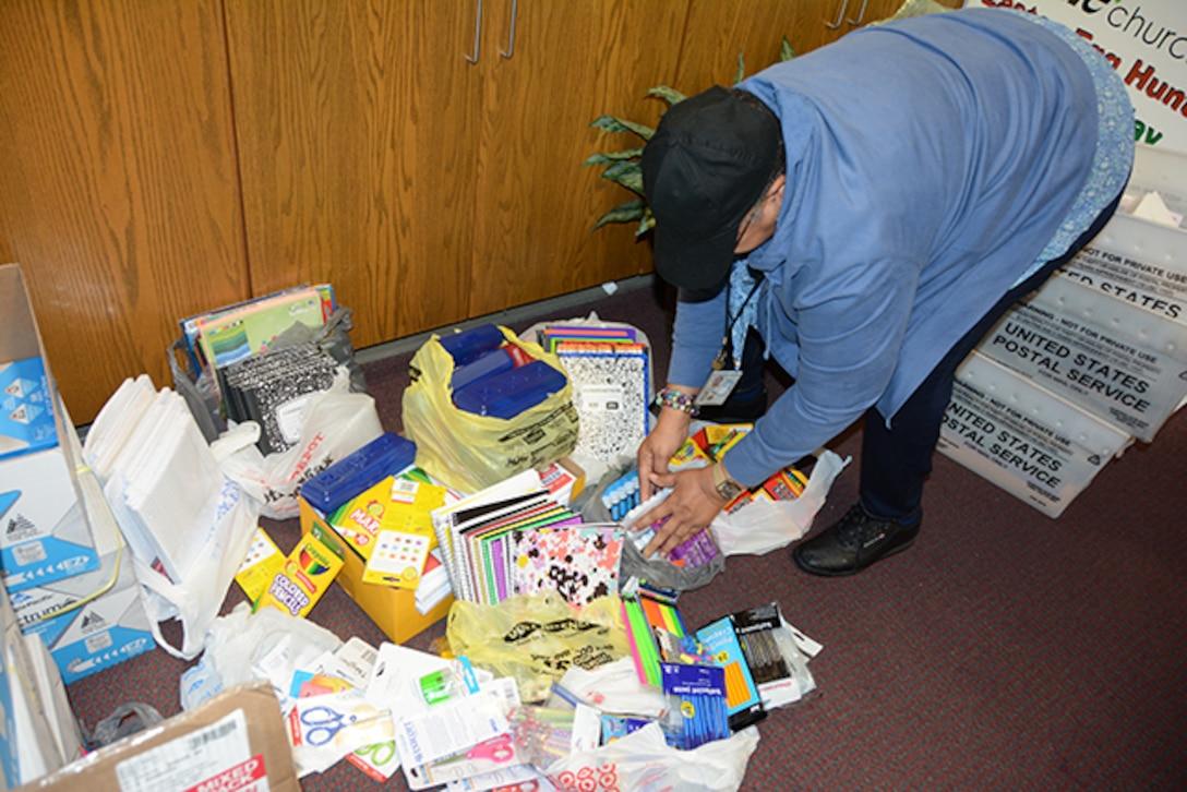 Employee sorts donated school supplies