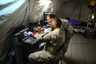 Two soldiers look at a computer screen.