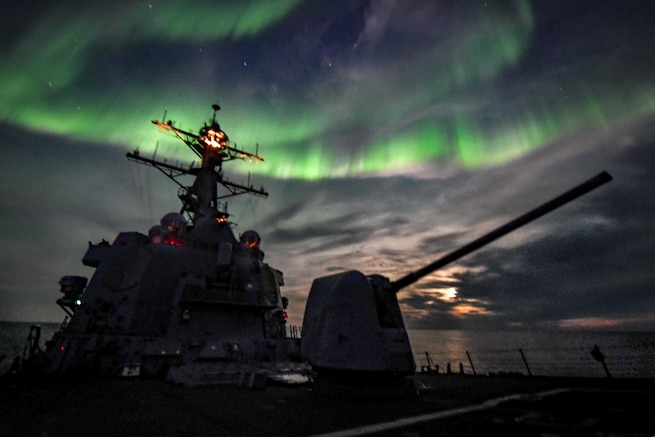 A destroyer in silhouette transits the ocean as northern lights flash green in the night sky.