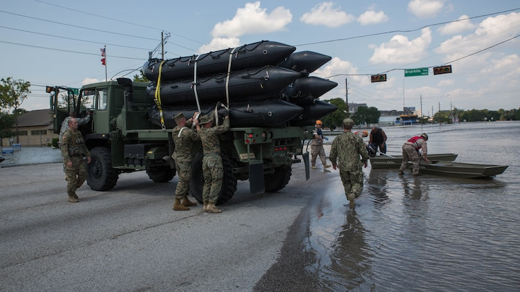U.S. Marines with Charlie Company, 4th Reconnaissance Battalion, 4th Marine Division, Marine Forces Reserve, unload their Marine Corps F470 Zodiacs Combat Rubber Raiding crafts on to a flooded street in Houston, Texas, Aug. 31, 2017. Marines from Charlie Company assisted rescue effort in wake of Hurricane Harvey by providing Zodiacs and personal to local law enforcement.