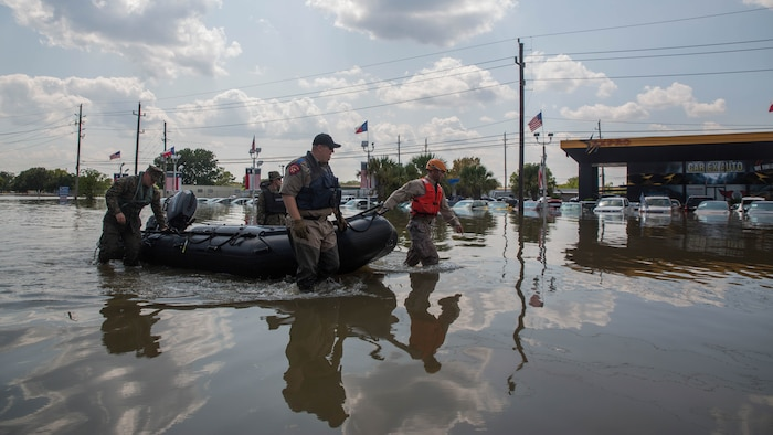 Marines with Charlie Company, 4th Reconnaissance Battalion, 4th Marine Division, Marine Forces Reserve, along with a member of the Texas Highway Patrol and Texas State Guard, pull a Marine Corps F470 Zodiacs Combat Rubber Raiding craft past a flooded car dealership in Houston, Texas, Aug. 31, 2017. Marines from Charlie Company assisted Texas Highway Patrolmen during rescue effort in wake of Hurricane Harvey which landed Aug. 25, 2017, and displaced over 30,000 people.