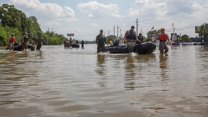 Marines with Charlie Company, 4th Reconnaissance Battalion, 4th Marine Division, Marine Forces Reserve, along with members of the Texas Highway Patrol and Texas State Guard, pull Marine Corps F470 Zodiacs Combat Rubber Raiding crafts through a flooded street in Houston, Texas, Aug. 31, 2017. Marines from Charlie Company assisted Texas Highway Patrolmen during rescue effort in wake of Hurricane Harvey which landed Aug. 25, 2017, and displaced over 30,000 people.