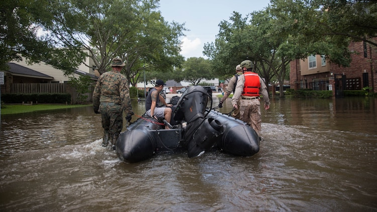 A Marine with Charlie Company, 4th Reconnaissance Battalion, 4th Marine Division, Marine Forces Reserve, along with a member of the Texas Highway Patrol and Texas State Guard, escort a man to higher ground, Houston, Texas, Aug. 31, 2017. Hurricane Harvey landed Aug. 25, 2017, flooding thousands of homes and displaced over 30,000 people.