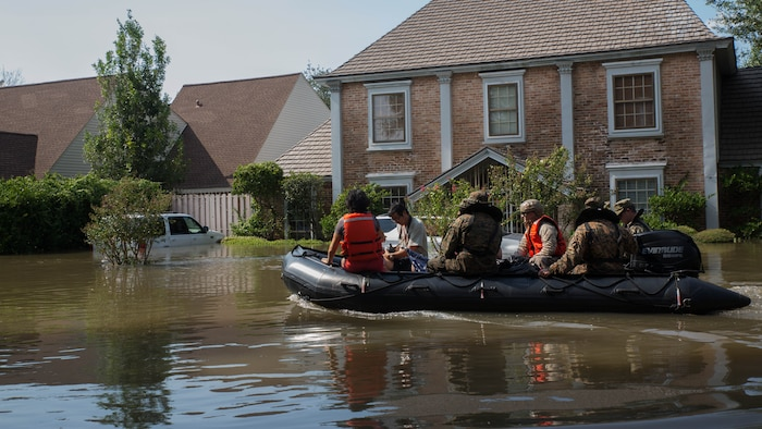 A Marine with Charlie Company, 4th Reconnaissance Battalion, 4th Marine Division, Marine Forces Reserve, along with a member of the Texas Highway Patrol and Texas State Guard, escort a couple to higher ground, Houston, Texas, Aug. 31, 2017. Hurricane Harvey landed Aug. 25, 2017, flooding thousands of homes and displaced over 30,000 people.