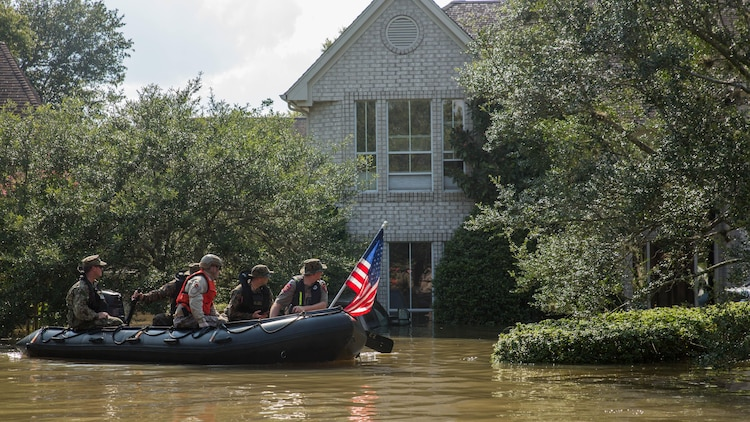 Marines with Charlie Company, 4th Reconnaissance Battalion, 4th Marine Division, Marine Forces Reserve, along with a member of the Texas Highway Patrol and Texas State Guard, patrol past a flooded house in Houston, Texas, Aug. 31, 2017. Hurricane Harvey landed Aug. 25, 2017, flooding thousands of homes and displaced over 30,000 people.