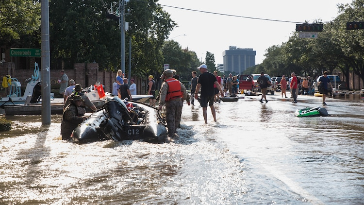 Marines with Charlie Company, 4th Reconnaissance Battalion, 4th Marine Division, Marine Forces Reserve, along with members of the Texas Highway Patrol and Texas State Guard, pull Marine Corps F470 Zodiacs Combat Rubber Raiding crafts through a flooded street in Houston, Texas, Aug. 31, 2017. Hurricane Harvey landed Aug. 25, 2017, flooding thousands of homes and displaced over 30,000 people.