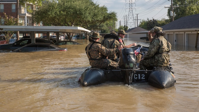 Marines with Charlie Company, 4th Reconnaissance Battalion, 4th Marine Division, Marine Forces Reserve, along with a member of the Texas Highway Patrol and Texas State Guard, navigate through a flooded parking lot in Houston, Texas, Aug. 31, 2017. Marines from Charlie Company assisted rescue effort in wake of Hurricane Harvey by providing Zodiacs and personal to local law enforcement.