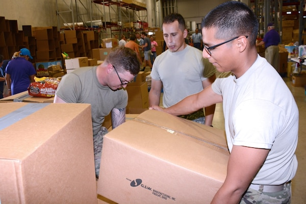 Spcs. Kellan Burdine, Juan Gonzalez and Isaias Santiago load boxes of donations onto a pallet at the San Antonio Book Bank warehouse Aug. 31