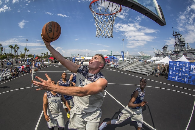 A sailor performs a layup at a basketball tournament with a ship in the background.