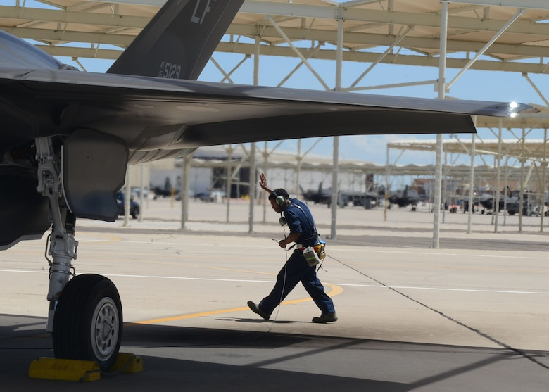 Airman 1st Class Eric Ruiz-Garcia, 63rd Aircraft Maintenance Unit crew chief, performs pre-flight inspections on an F-35A Lightning II at Luke Air Force Base, Ariz., Aug. 22, 2017. Ruiz-Garcia wore air sampling devices and thermal stress monitors during the launch and recovery of the F-35. The purpose of the test is to collect real time data of the air quality and the core temperatures of the maintainers during a launch. (U.S. Air Force photo/Senior Airman James Hensley)