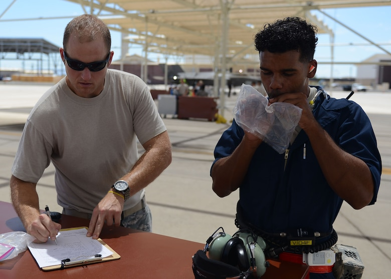Maj. Jamie Kurzdorfer, School of Aerospace Medicine Force Health Protection branch chief (left), annotates the time when Airman 1st Class Eric Ruiz-Garcia, 63rd Aircraft Maintenance Unit crew chief, gives an air sample at Luke Air Force Base, Ariz., Aug. 22, 2017. Ruiz-Garcia also wore air sampling devices and thermal stress monitors during the launch and recovery of an F-35A Lightning II. The purpose of the test is to collect real time data of the air quality and the core temperatures of the maintainers during a launch. (U.S. Air Force photo/Senior Airman James Hensley)