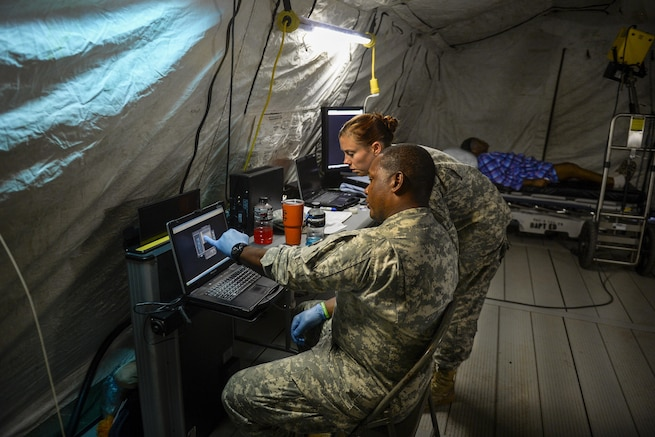 Two soldiers look at an X-ray in a field hospital in a parking lot.