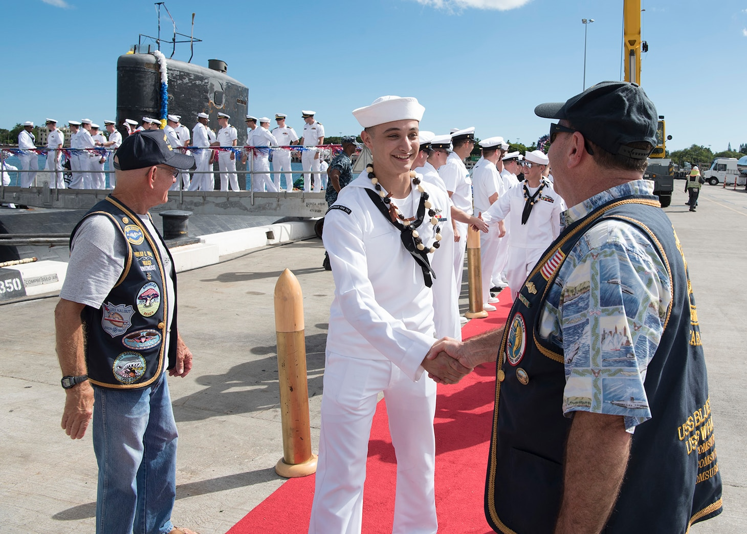 Retired submariners from the U.S. Submarine Veterans Bowfin Base chapter welcome home Sailors from the Los Angeles-class attack submarine USS Columbus (SSN 762). .(U.S. Navy Photo by Mass Communication Specialist 2nd Class Shaun Griffin/Released)