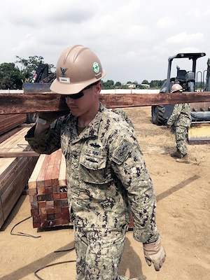 Navy Petty Officer 2nd Class James Herrera with Naval Mobile Construction Battalion 1 offloads lumber materials received for construction of a multipurpose building project in Douala, Cameroon, in March. Lumber, gravel and electrical parts are among the many supplies DLA buys locally for troops stationed in Africa.