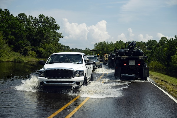 Military vehicles and civilian vehicles drive though a flooded street.