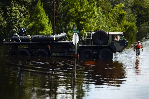 A military vehicle drives through flood waters on a street.