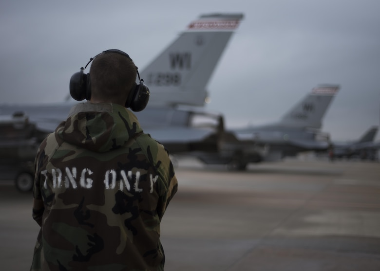 U.S. Air Force Staff Sgt. Andrew Ausel, 115th Aircraft Maintenance Squadron weapons load crew member, assigned to the Wisconsin Air National Guard, watches as four F-16 Fighting Falcons prepare to taxi down the runway at Kunsan Air Base, Republic of Korea, Aug. 22, 2017. The 115th Fighter Wing participated in a regularly-scheduled operational readiness exercise, Beverly Pack 17-3, as part of a Theater Security Package deployment to Kunsan. Pacific Air Forces TSPs signify a continued commitment to regional stability and security, while allowing units to train in the Pacific theater. (U.S. Air Force photo by Staff Sgt. Victoria H. Taylor/Released)