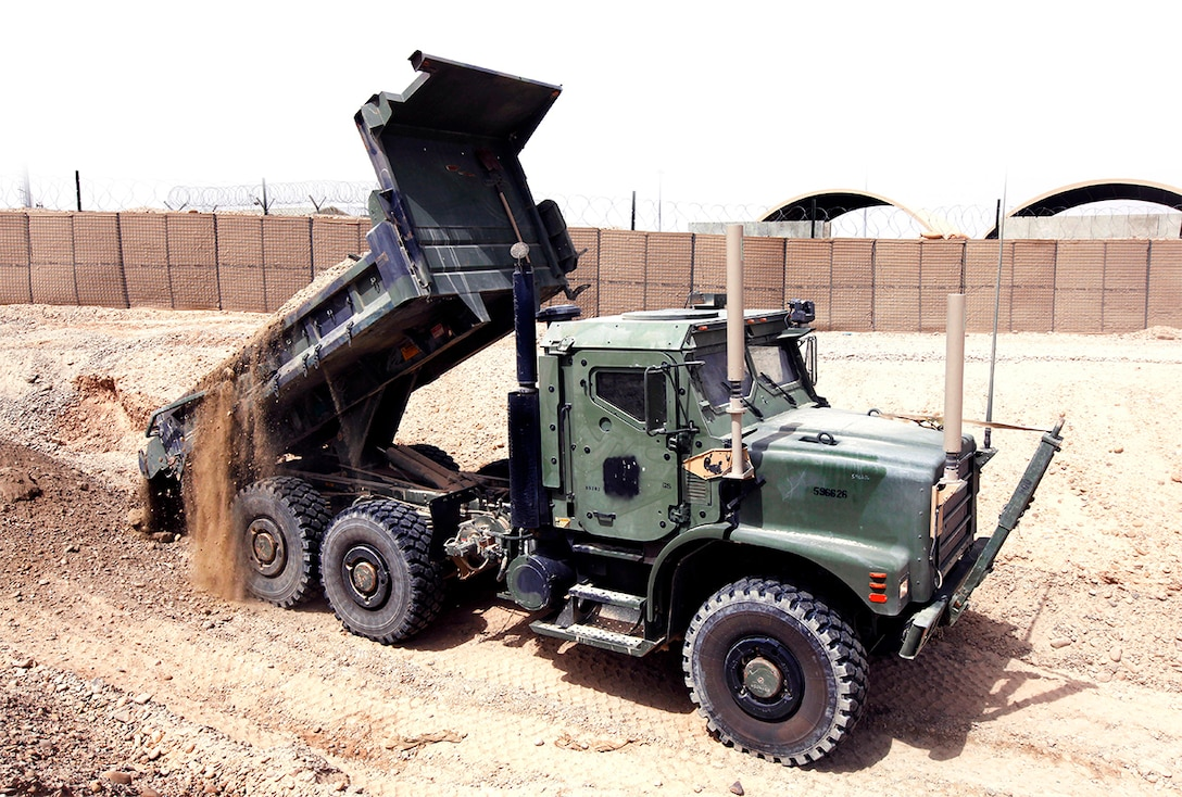 Marines use a dump-truck variation of the Medium Tactical Vehicle Replacement at Camp Bastion, Helmand Province, Afghanistan, to level the ground and create a staging area for their equipment.