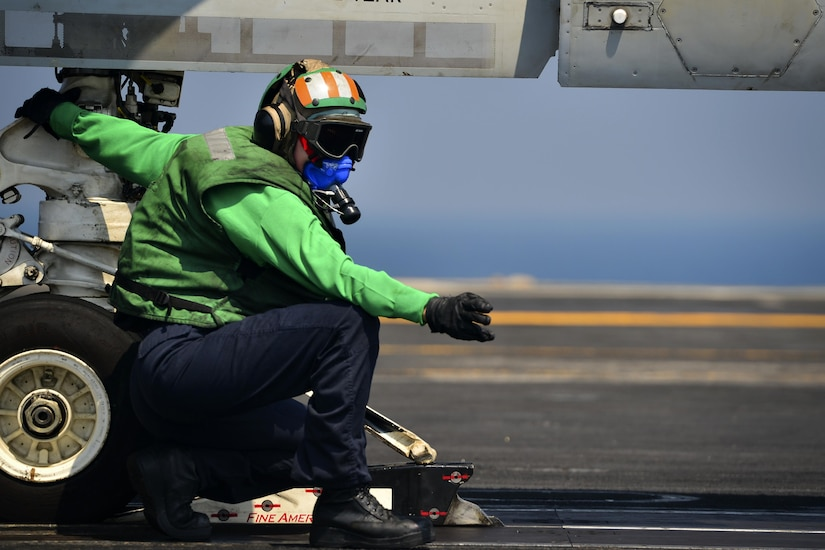 A sailor wearing heat gear makes signals while holding onto the wheel of an aircraft.