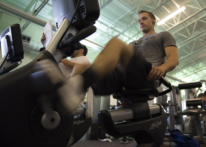 U.S. Air Force 1st Lt. James LaCoste, 633rd Force Support Squadron chief career development element, uses a recumbent exercise bike at Joint Base Langley-Eustis, Va., July 20, 2017. While training for a bodybuilding competition, LaCoste would drop his caloric intake from 4,000 to 2,000 calories and used cardio workouts 8341to continue his weight loss. (U.S. Air Force photo by Staff Sgt. J.D. Strong II)