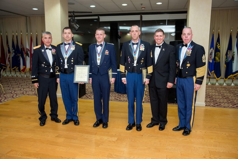 Maj. James Crawford, 67th Cyberspace Operations Group (center left), poses with Lt. Gen. Paul Nakasone, Commanding General of U.S. Army Cyber Command (left), and other winners of the 2017 AFCEA Saint Isidore Army Cyber Award at the Army Cyber Ball Aug. 19 on Fort Belvoir, Va. Crawford was the only Airman to win this award, which is given to those who make significant contributions to the promotion of the Army Cyber mission.