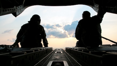 Army Sgt. 1st Class Roy Chandler, left, and Spc. Benjamin Grogan, assigned to the Alabama Army National Guard's Bravo Company, 1st Battalion, 169th Aviation Regiment, sit on the tail of a CH-47 Chinook helicopter en route to deliver hay bales to cattle that have been stranded by Hurricane Harvey near Hampshire, Texas, Sep. 3, 2017. Texas Army National Guard photo by Spc. Dustin Biven