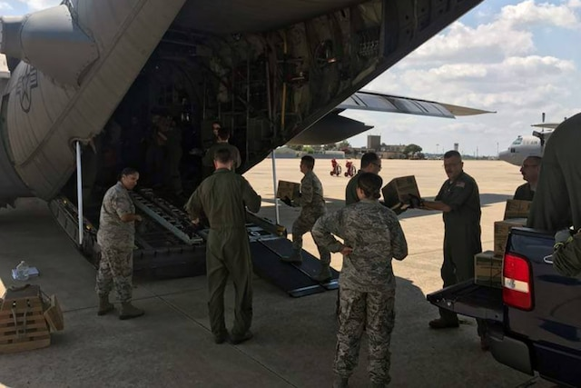 Guard members load relief supplies on a C-130 aircraft.