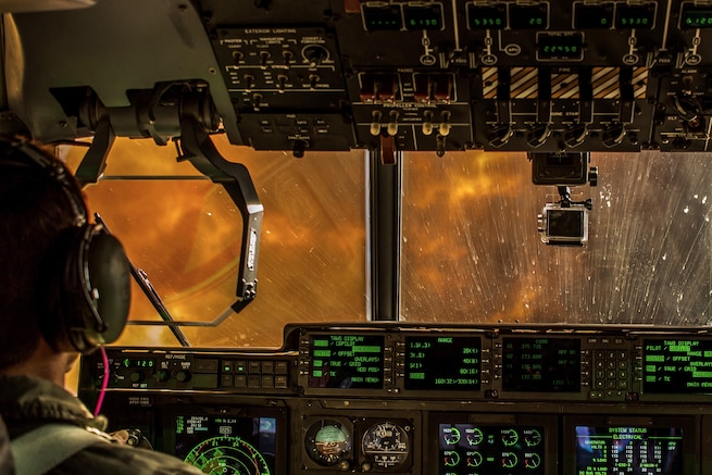 Flames and smoke are visible from the cockpit of an aircraft.