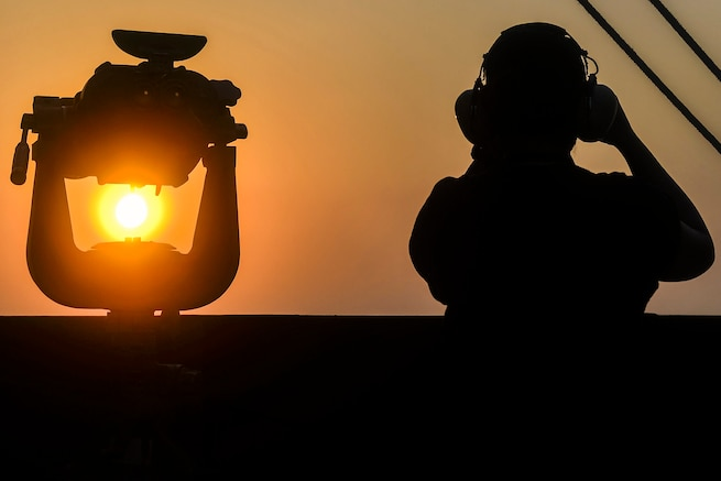 A sailor, shown from the back in silhouette, looks out from the deck of an aircraft carrier.