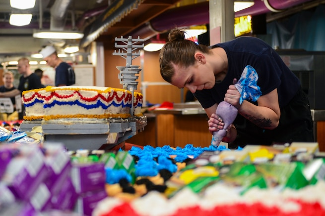 A sailor ices rows of cupcakes sitting on a table.